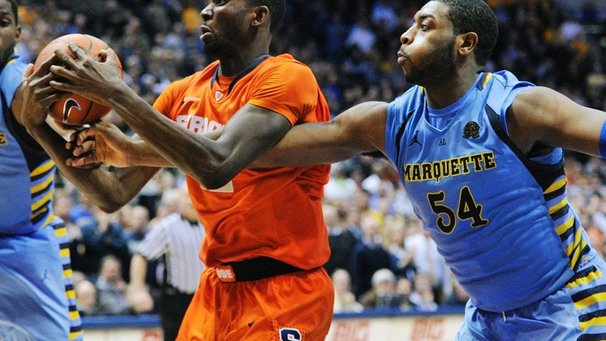 Syracuse's Baye Keita, left, and Marquette's Davante Gardner (54) fight for a rebound during the second half of an NCAA college basketball game, Monday, Feb. 25, 2013, in Milwaukee. Marquette won 74-71. (AP Photo/Jim Prisching)