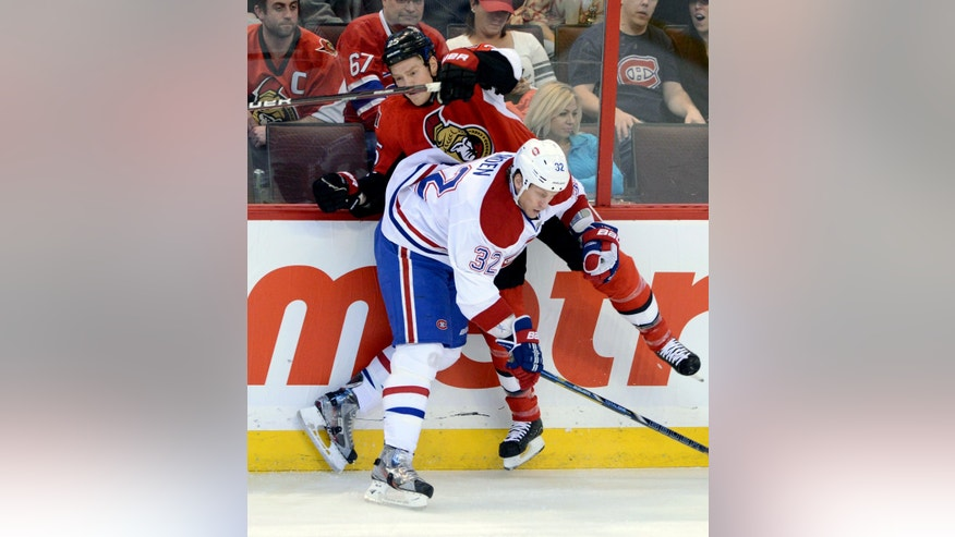 Ottawa Senators' Chris Neil is hit by Montreal Canadiens' Travis Moen during the first period of an NHL hockey game in Ottawa, Ontario, on Monday, Feb 25, 2013. (AP Photo/The Canadian Press, Sean Kilpatrick)