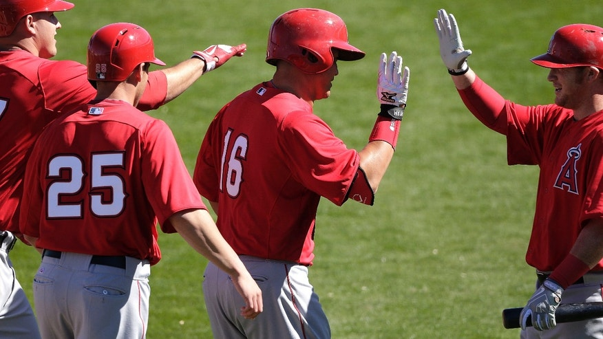 Los Angeles Angels' Hank Conger (16) celebrates his three-run home run with Mike Trout, left, Peter Bourjos (25) and Kole Calhoun, right, during an exhibition spring training baseball game against the Seattle Mariners on Monday, Feb. 25, 2013, in Peoria, Ariz. (AP Photo/Charlie Riedel)