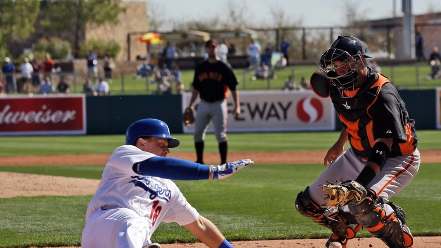 Los Angeles Dodgers' Tim Federowicz, left, scores on a double by Skip Schumaker as San Francisco Giants catcher Guillermo Quiroz, right, bobbles the throw during the second inning of an exhibition spring training baseball game on Tuesday, Feb. 26, 2013 in Glendale. Ariz. (AP Photo/Marcio Jose Sanchez)