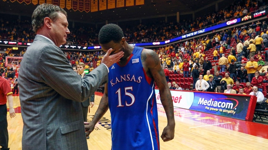 Kansas head coach Bill Self, left, pats guard Elijah Johnson (15) on the face after Johnson scored 39 points in their 108-96 overtime win against Iowa State in an NCAA college basketball game, Monday, Feb. 25, 2013, in Ames, Iowa. Self earned his 500th career victory with the win. (AP Photo/Justin Hayworth)