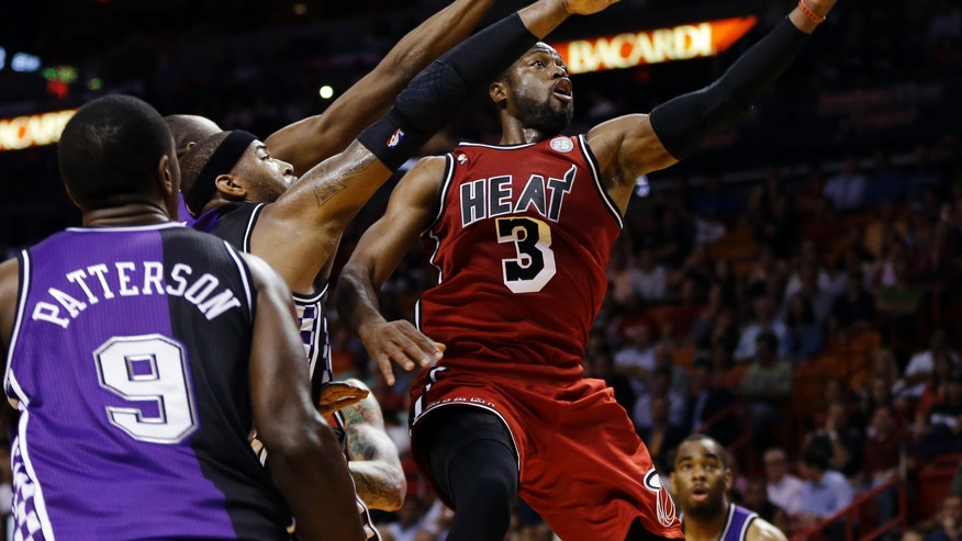 Sacramento Kings' Patrick Patterson (9) watches as DeMarcus Cousins (15) tries to block Miami Heat's Dwyane Wade (3) during the first half of an NBA basketball game in Miami, Tuesday, Feb. 26, 2013. (AP Photo/J Pat Carter)