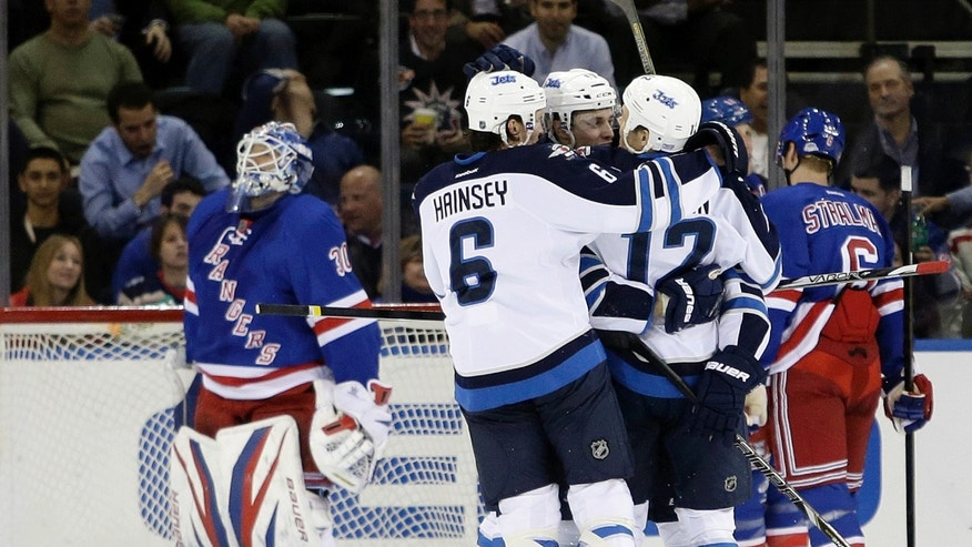Winnipeg Jets players including Ron Hainsey (6) celebrate a goal by Olli Jokinen (12) during the second period of an NHL hockey game against the New York Rangers on Tuesday, Feb. 26, 2013, in New York. Rangers goalie Henrik Lundqvist, of Sweden, left, watches. (AP Photo/Frank Franklin II)