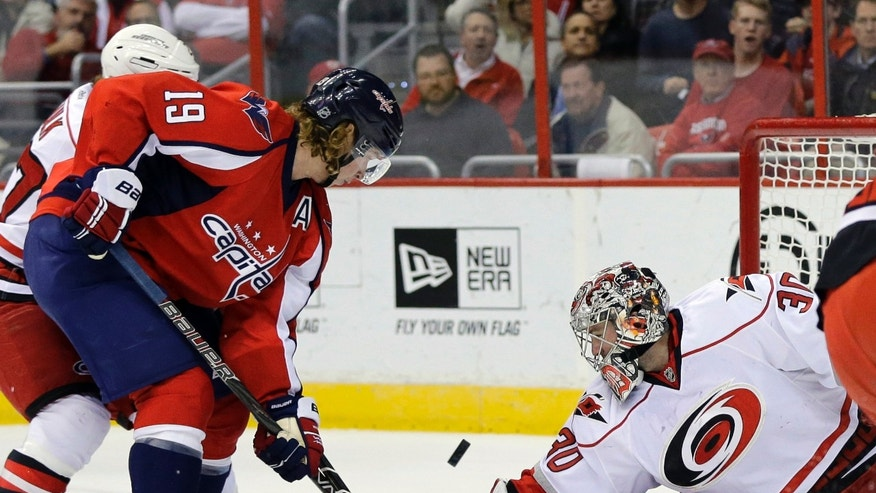 Washington Capitals center Nicklas Backstrom (19), from Sweden, shoots over Carolina Hurricanes goalie Cam Ward (30) for a goal in the first period of an NHL hockey game Tuesday, Feb. 26, 2013, in Washington. (AP Photo/Alex Brandon)