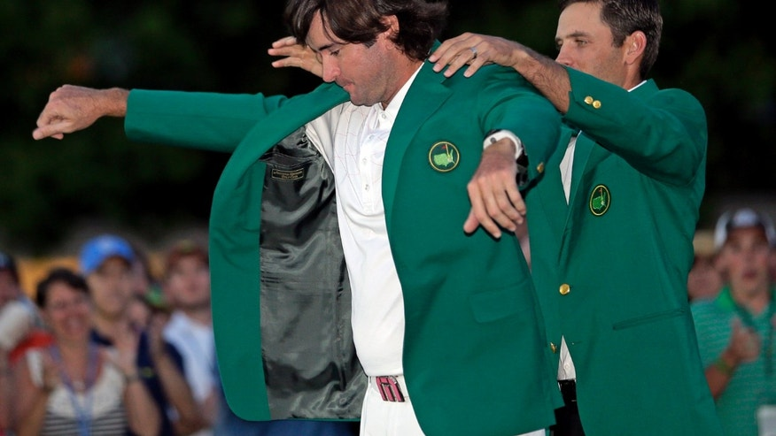 FILE - In this April 8, 2012 file photo, Charl Schwartzel, right, of South Africa, helps Bubba Watson put on the green jacket after winning the Masters golf tournament in Augusta, Ga. There's one palm tree at Augusta National, and it takes on new meaning for Masters champion Bubba Watson. (AP Photo/David J. Phillip, File)