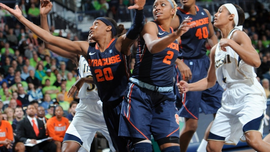 Syracuse guard Brittany Sykes (20) grabs a rebound as Syracuse guard Elashler Hall and Notre Dame guard Skylar Diggins, right, watch during the first half of an NCAA college basketball game Tuesday, Feb. 26, 2013, in South Bend, Ind. (AP Photo/Joe Raymond)