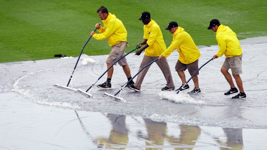 Grounds crew workers push water off the tarp before an exhibition spring training baseball game between the Pittsburgh Pirates and the Baltimore Orioles, Tuesday, Feb. 26, 2013, in Bradenton, Fla. (AP Photo/Charlie Neibergall)