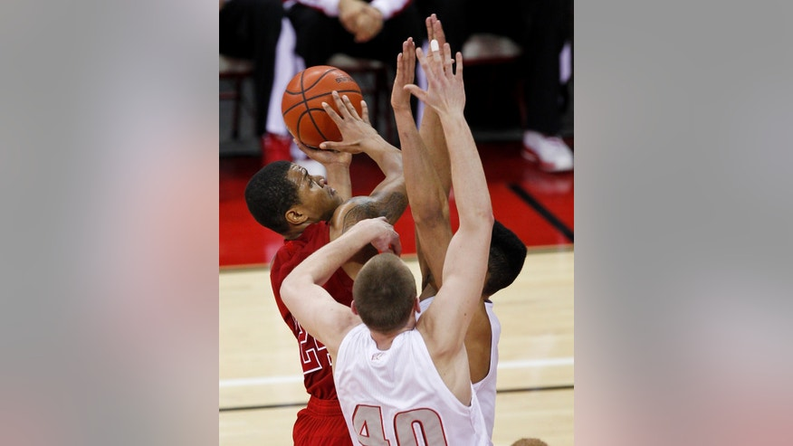 Nebraska's Dylan Talley shoots against Wisconsin's Jared Bergrren (40) and Ryan Evans during the first half of an NCAA college basketball game Tuesday, Feb. 26, 2013, in Madison, Wis. (AP Photo/Andy Manis)