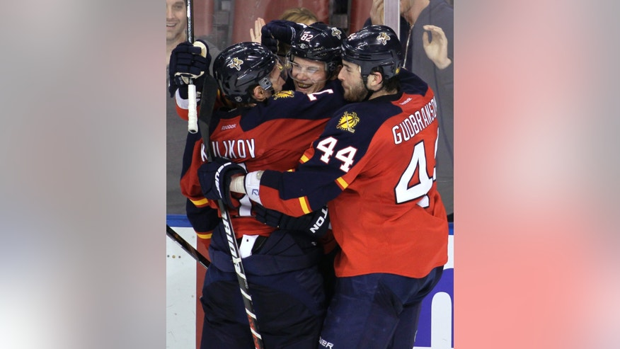 Florida Panthers' Tomas Kopecky, center, of Slovakia, celebrates with teammates Dmitry Kulikov, left, and Erik Gudbranson (44) after Kopecky's third goal of a hat trick, an empty-netter against the Pittsburgh Penguins during the third period of an NHL hockey game, Tuesday, Feb. 26, 2013, in Sunrise, Fla. The Panthers won 6-4. (AP Photo/Luis M. Alvarez)