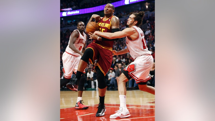 Chicago Bulls' Joakim Noah (13) slaps ball from the hands of Cleveland Cavaliers' Marreese Speights during the second quarter of an NBA basketball game, Tuesday, Feb. 26, 2013, in Chicago.(AP Photo/Charles Cherney)