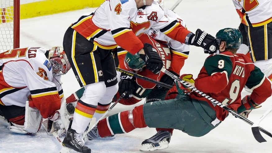Calgary Flames' Jay Bouwmeester (4) sends Minnesota Wild's Mikko Koivu, of Finland, to the ice as Flames goalie Joey MacDonald, left, stops a shot in the first period of an NHL hockey game Tuesday, Feb. 26, 2013, in St. Paul, Minn. (AP Photo/Jim Mone)