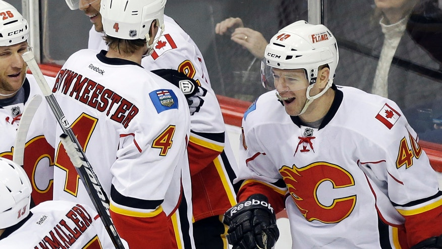 Calgary Flames' Alex Tanguay, right, celebrates his goal with teammates in the first period of an NHL hockey game against the Minnesota Wild on Tuesday, Feb. 26, 2013, in St. Paul, Minn. (AP Photo/Jim Mone)