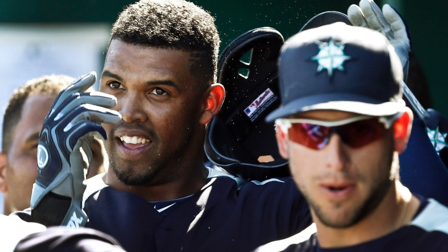Seattle Mariners' Carlos Peguero, left, takes off his batting helmet after celebrating his home run against the Cleveland Indians with teammates, including Alex Liddi, right, in the fourth inning of an exhibition spring training baseball game, Wednesday, Feb. 27, 2013, in Goodyear, Ariz.(AP Photo/Ross D. Franklin)