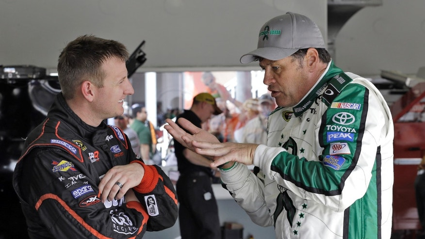 Michael Waltrip, right, gestures as he talks to Michael McDowell in the garage area during practice for the NASCAR Sprint Cup Series Daytona 500 auto race Saturday, Feb. 23, 2013, at the Daytona International Speedway in Daytona Beach, Fla. (AP Photo/Chris O'Meara)