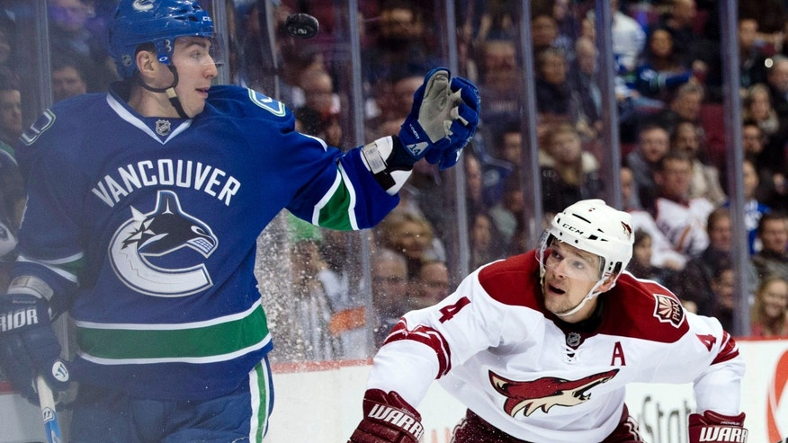 Phoenix Coyotes' Zbynek Michalek, right, watches Vancouver Canucks' Alex Burrows try and grab the puck during the first period of their NHL hockey game, Tuesday, Feb. 26, 2013, in Vancouver, British Columbia. (AP Photo/The Canadian Press, Jonathan Hayward)