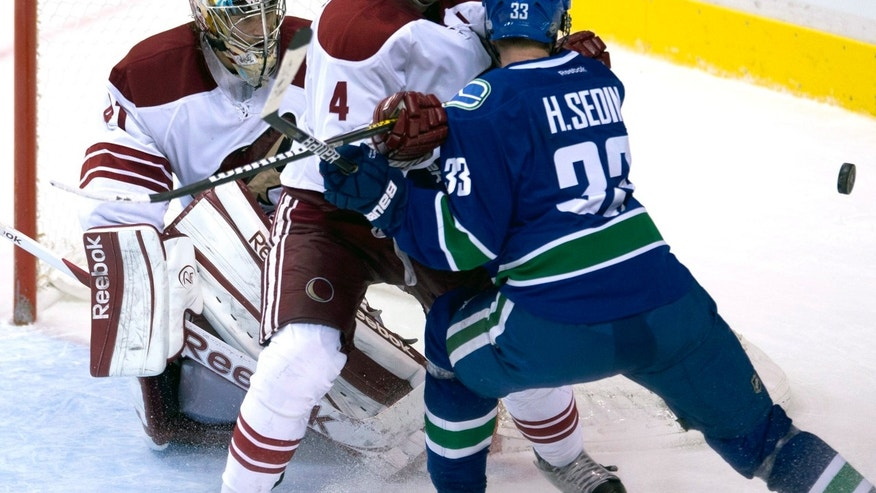 Phoenix Coyotes' Zbynek Michalek (4) tries to clear Vancouver Canucks' Henrik Sedin (33) from in front of the net as Phoenix Coyotes goalie Mike Smith (41) looks on during second period of NHL hockey action at Rogers Arena in Vancouver, British Columbia, Tuesday Feb.26, 2013. (AP Photo/THE CANADIAN PRESS,Jonathan Hayward)
