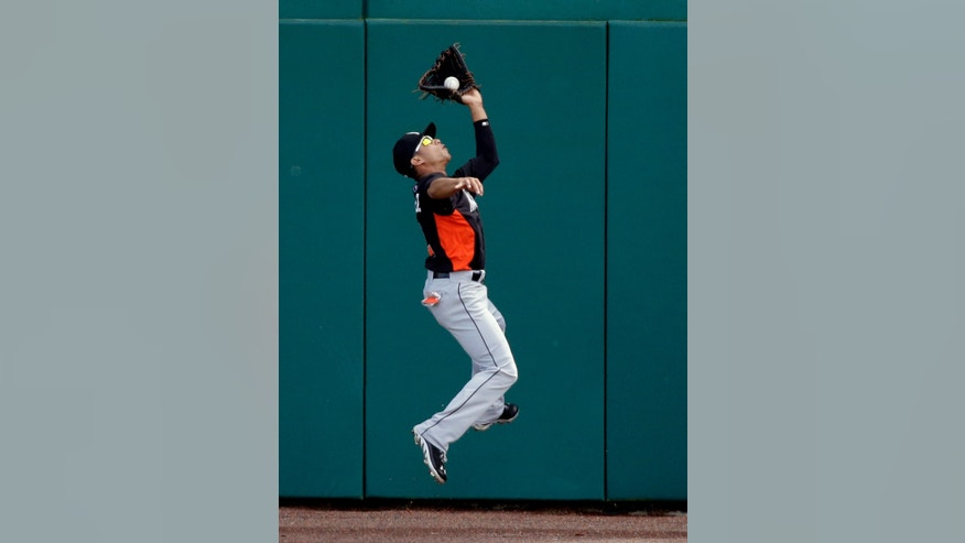 Miami Marlins center fielder Gorkys Hernandez leaps near the wall to catch a fly ball hit by Washington Nationals' Zach Walters during the third inning of an exhibition spring training baseball game Wednesday, Feb. 27, 2013, in Viera, Fla. (AP Photo/David J. Phillip)