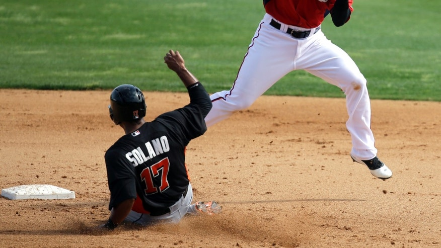 Miami Marlins' Donovan Solano (17) steals second base as Washington Nationals infielder Zach Walters, right, handles the throw during the sixth inning of an exhibition spring training baseball game Wednesday, Feb. 27, 2013, in Viera, Fla. (AP Photo/David J. Phillip)