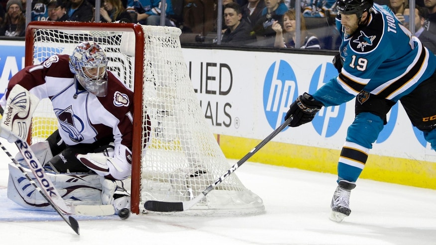 CORRECTS MONTH TO FEBRUARY, NOT MARCH - Colorado Avalanche goalie Semyon Varlamov, left, blocks a shot from San Jose Sharks' Joe Thornton (19) during the first period of an NHL hockey game Tuesday, Feb. 26, 2013, in San Jose, Calif. (AP Photo/Ben Margot)