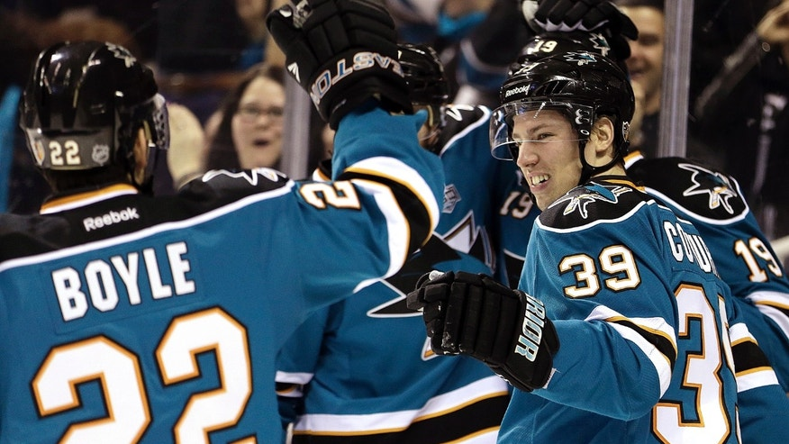 CORRECTS MONTH TO FEBRUARY, NOT MARCH - San Jose Sharks' Logan Couture (39) is congratulated by Ryane Boyle (29) after Couture scored a goal against the Colorado Avalanche during the first period of an NHL hockey game Tuesday, Feb. 26, 2013, in San Jose, Calif. (AP Photo/Ben Margot)