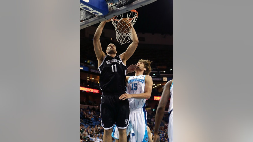 Brooklyn Nets center Brook Lopez (11) slam dunks over his twin brother, New Orleans Hornets center Robin Lopez (15) in the first half of an NBA basketball game in New Orleans, Tuesday, Feb. 26, 2013. (AP Photo/Gerald Herbert)