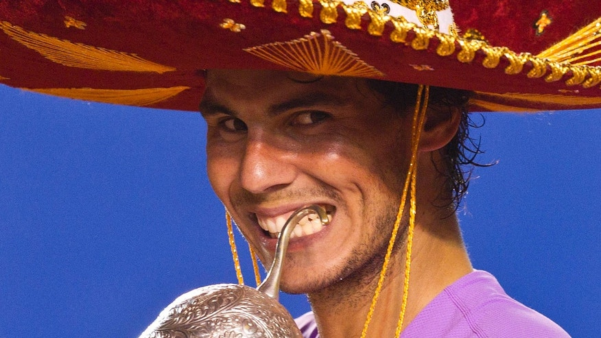 "Wearing a traditional Mexican ""sombrero"",  Spain´s Rafael Nadal bites the trophy for the cameras after beating Spain's David Ferrer in the final round match of the Mexico Open tennis tournament in Acapulco, Mexico, Saturday, March  2, 2013. Nadal blasted past top seed and defending champion David Ferrer 6-0, 6-2 in Saturday's final  in a powerful performance that indicated he has quickly returned to near his best after a long-term knee injury.(AP Photo/Christian Palma)"