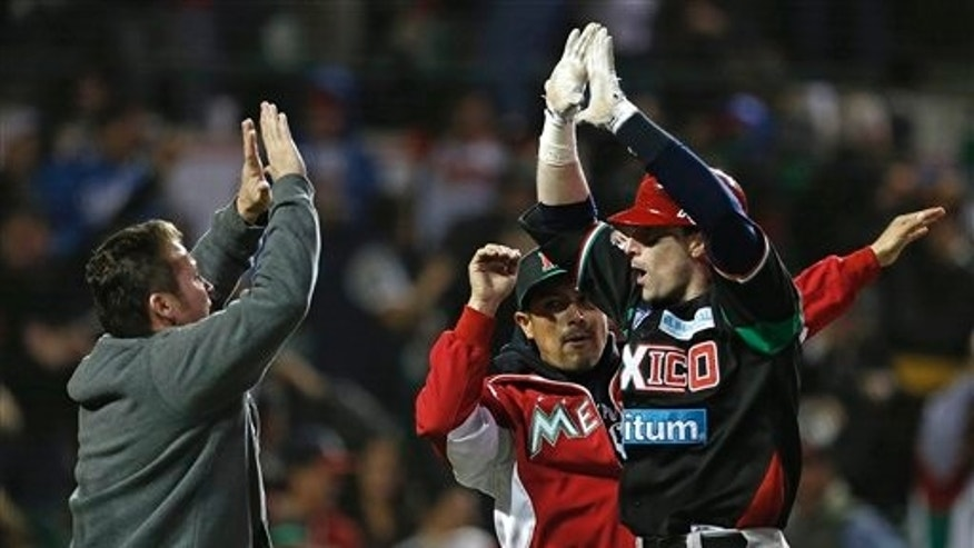 Mexico's Douglas Clark, right, high-fives with teammate Karim Garcia, left, after hitting a solo home run that represented the winning run in the 18th inning of the championship game against the Dominican Republic in the Caribbean Baseball Series in Hermosillo, Mexico, in the early hours of Friday, Feb. 8, 2013. Mexico won 4-3 in an 18-inning game. (AP Photo/Andres Leighton)