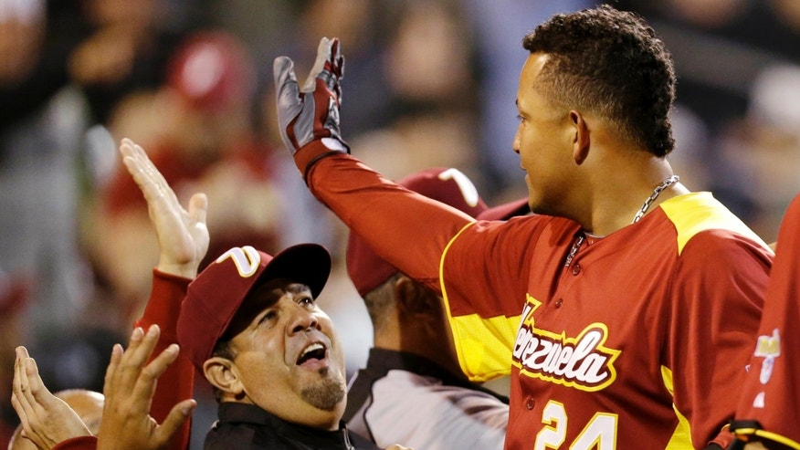 Venezuela manager Luis Sojo, left, reacts as Miguel Cabrera is congratulated after hitting a home run against Miami Marlins non-roster invitee pitcher Jordan Smith during the seventh inning of an exhibition spring training baseball game, Tuesday, March 5, 2013, in Jupiter, Fla. (AP Photo/Julio Cortez)