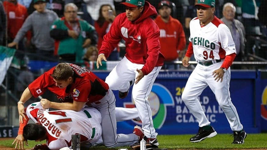 March 9, 2013: Canada's Jay Johnson, top left, and Mexico's Eduardo Arredondo fight during the ninth inning of a World Baseball Classic game in Phoenix.