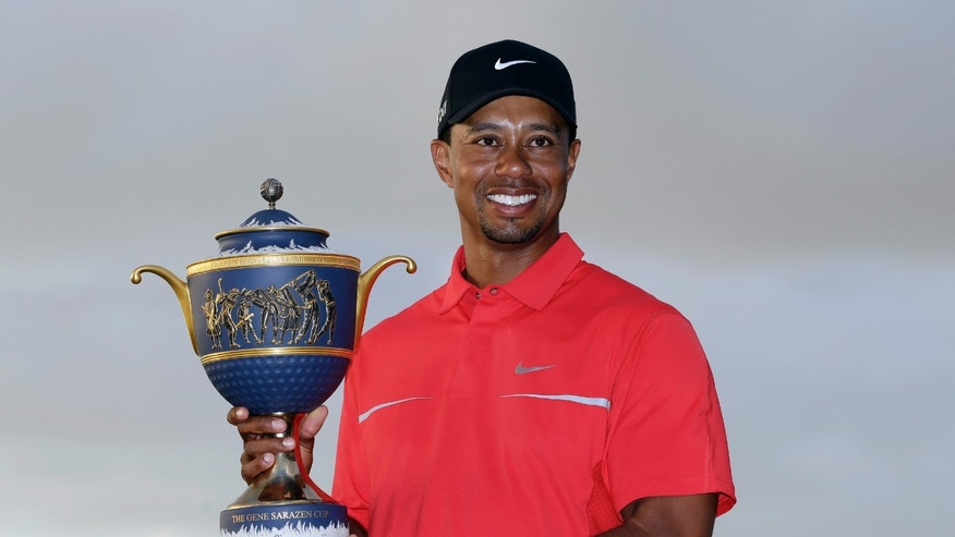 March 10, 2013: Tiger Woods holds the Gene Sarazen Cup for winning the Cadillac Championship golf tournament in Doral, Fla.