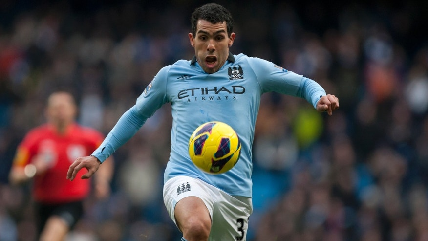 FILE- English Premier League Manchester City soccer player Carlos Tevez in action at The Etihad Stadium in Manchester, England, in this file photo dated Sunday Feb. 24, 2013.  Tevez has been arrested in England on suspicion of driving his car while disqualified from driving, police sources confirmed Friday March 8, 2013.  Tevez has been released on police bail pending further inquiries.(AP Photo/Jon Super, File)