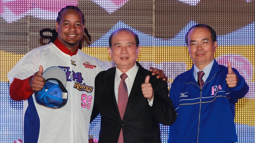 Former MLB star Manny Ramirez, left, poses for the media with head of E-United Group Lin Yi-shou, center, and EDA Rhinos' team manager Yang Sun-long after signing a short-term contract to play on the EDA Rhinos in Taiwan's professional baseball league in Kaohsiung, Taiwan, Tuesday, March 12, 2013. The EDA Rhinos say Ramirez will earn $25,000 a month to appear with the team during this year's March-November season. (AP Photo/Wally Santana)