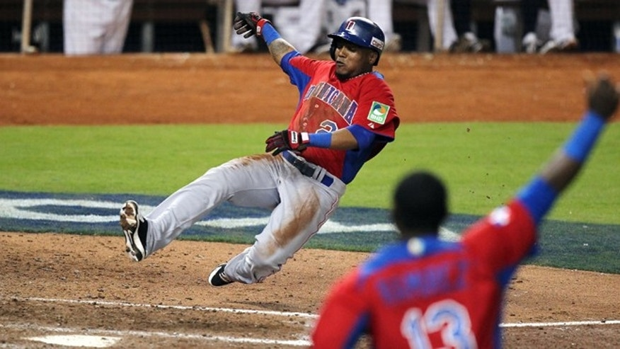 Dominican Republic's Erick Aybar slides safely into home on an RBI single by Jose Reyes against the United States during the ninth inning of their second-round game in the World Baseball Classic in Miami, Thursday, March 14, 2013. The Dominican Republic won 3-1. (AP Photo/El Nuevo Herald, David Santiago)  MAGS OUT