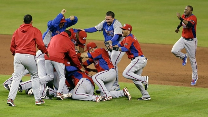 Puerto Rico players celebrate after defeating the United States 4-3 during a second-round elimination game of the World Baseball Classic, Friday, March 15, 2013, in Miami. (AP Photo/Wilfredo Lee)