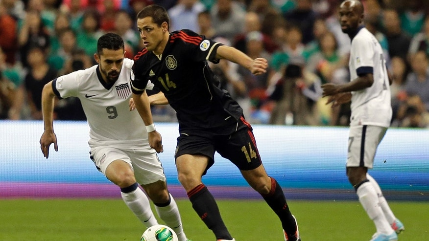 Mexico's Javier Hernandez, center, and United States' Herculez Gomez, left, vie for the ball during a 2014 World Cup qualifying match at the Aztec stadium in Mexico City, Tuesday, March 26, 2013. (AP Photo/Eduardo Verdugo)