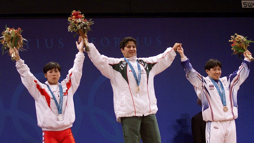 Gold medalist Soraya Jimenez of Mexico, center, is flanked by silver medalist Song Hui Ri of North Korea, left, and bronze medalist Khassaraporn Suta of Thailand in the podium of the women's 58 kg weightlifting competition of the Summer Olympic Games in Sydney, Australia, on Sept. 18, 2000 .