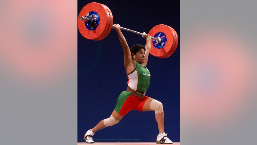 FILE - In this Sept. 18, 2000 file photo, Soraya Jimenez of Mexico, completes a final lift to win the gold medal in the clean and jerk event of the women's 58 kg weightlifting competition at the Summer Olympic Games in Sydney, Australia. Jimenez, the first woman to win an Olympic gold medal for her country, died of a heart attack on Thursday, March 28, 2013 in Mexico City. She was 35. (AP Photo/David Guttenfelder, File)