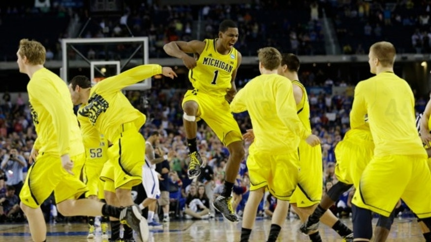 March 29, 2013: Michigan's Glenn Robinson III (1) and teammates celebrate after beating Kansas 87-85 in overtime of a regional semifinal game in the NCAA college basketball tournament in Arlington, Texas.
