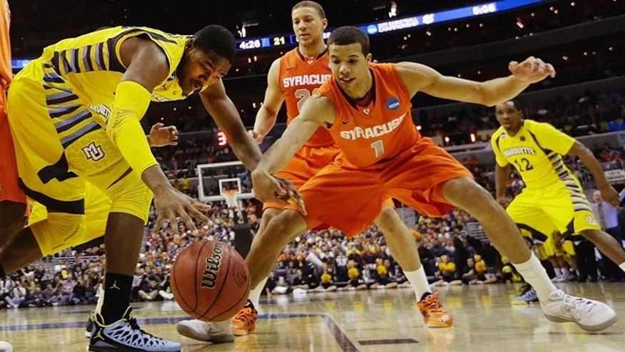 March 30, 2013: Marquette forward Steve Taylor Jr., (25) and Syracuse guard Michael Carter-Williams (1) reach for a loose ball during the first half of the East Regional final in the NCAA men's college basketball tournament in Washington.