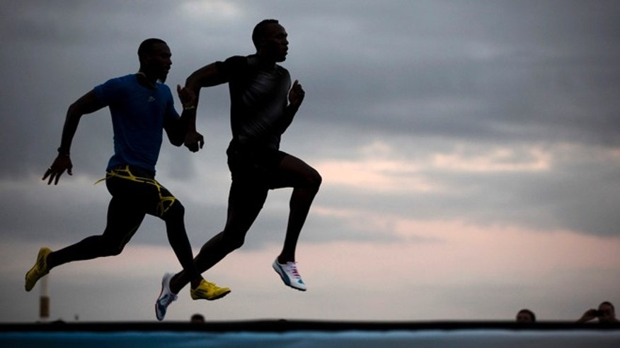 "Jamaican Olympic gold medalist Usain Bolt, right, runs with Antigua and Barbuda sprinter Daniel Bailey during a training session of the ""Mano a Mano"" challenge at Copacabana beach in Rio de Janeiro, Brazil, Friday, March 29, 2013. Bolt will compete Sunday on a track specially built at the famous beach, challenging Bailey, Ecuador's Alex Quinones and a Brazilian athlete from a local qualifier. (AP Photo/Felipe Dana)"
