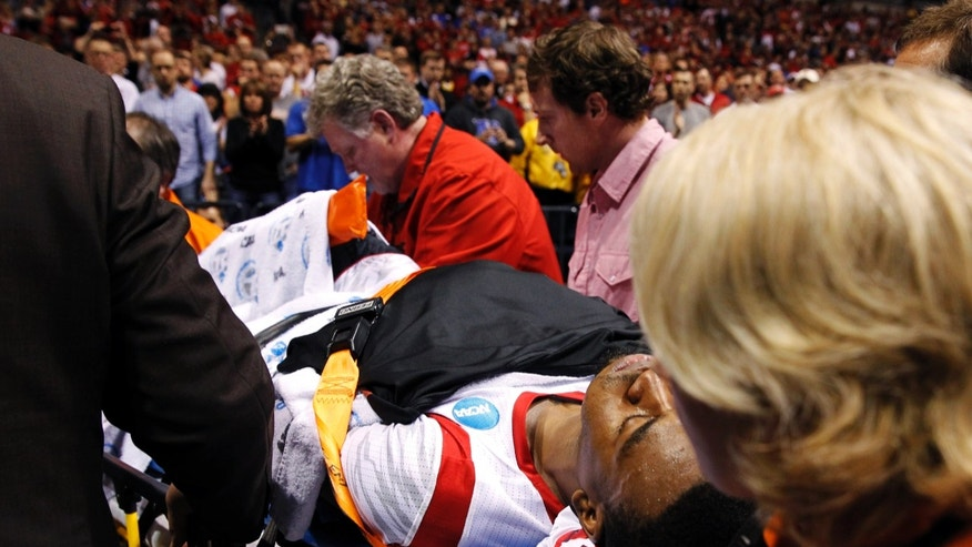 Louisville guard Kevin Ware is taken off the court on a stretcher after badly injuring his lower right leg during the first half of the Midwest Regional final against Duke in the NCAA college basketball tournament, Sunday, March 31, 2013, in Indianapolis. (AP Photo/Darron Cummings)
