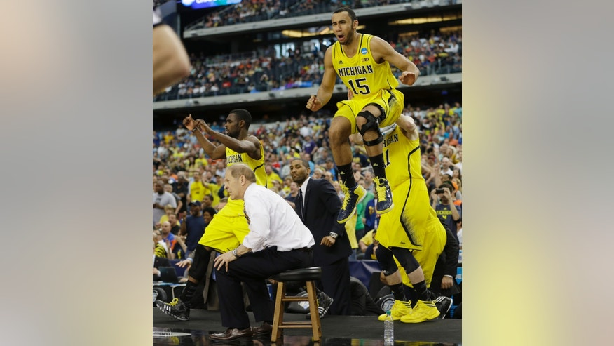 Michigan head coach John Beilein and players including Jon Horford (15) react against Florida during the second half of a regional final game in the NCAA college basketball tournament, Sunday, March 31, 2013, in Arlington, Texas. Michigan won 79-59. (AP Photo/David J. Phillip)