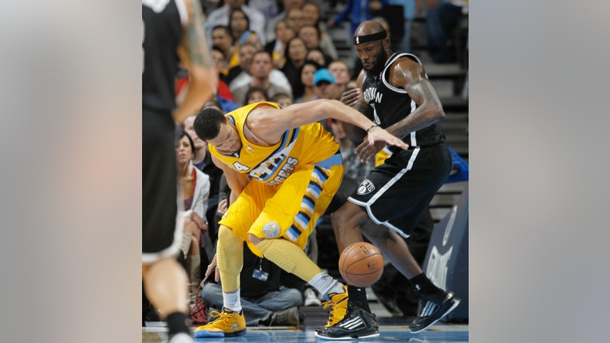 Denver Nuggets forward JaVale MGee, left, tries to pick up a loose ball as Brooklyn Nets forward Reggie Evans defends during the third quarter of the Nuggets' 109-87 victory in an NBA basketball game in Denver on Friday, March 29, 2013. (AP Photo/David Zalubowski)