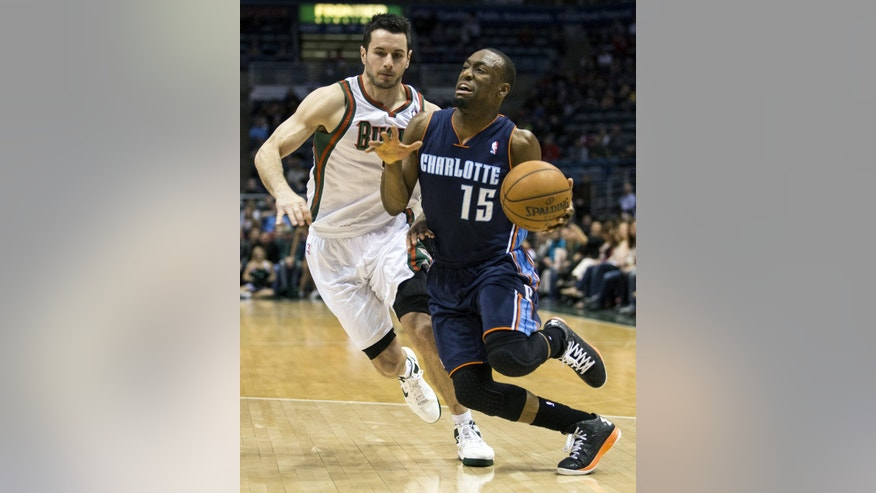Milwaukee Bucks' J.J. Redick chases Charlotte Bobcats' Kemba Walker as he drives to the hoop during the first half of an NBA basketball game Monday, April 1, 2013, in Milwaukee. (AP Photo/Tom Lynn)
