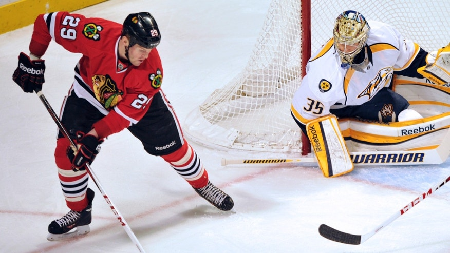 Chicago Blackhawks' Bryan Bickell (29) looks to shoot the puck on Nashville Predators' Pekka Rinne (35) during the first period of an NHL hockey game Monday, April 1, 2013, in Chicago. (AP Photo/Jim Prisching)