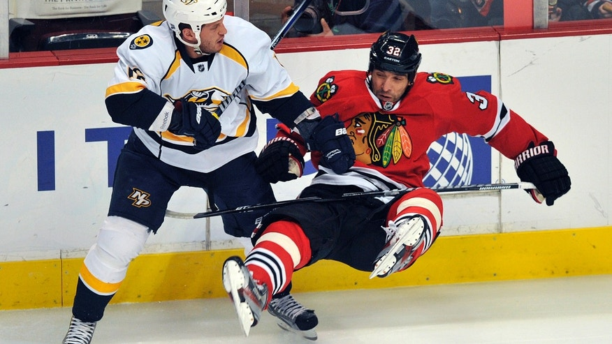 Nashville Predators' Richard Clune left, checks the Chicago Blackhawks' Michal Rozsival during the first period of an NHL hockey game Monday, April 1, 2013, in Chicago. (AP Photo/Jim Prisching)