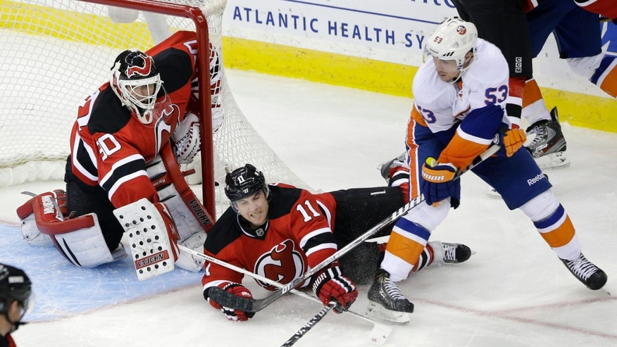 New Jersey Devils goalie Martin Brodeur (30) and Stephen Gionta (11) defend as New York Islanders' Casey Cizikas (53) tries to score a goal during the second period of an NHL hockey game Monday, April 1, 2013, in Newark, N.J. (AP Photo/Mel Evans)