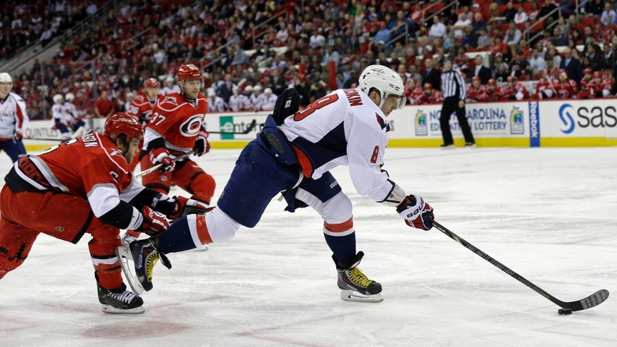 Washington Capitals' Alex Ovechkin (8), of Russia, controls the puck as Carolina Hurricanes' Tim Gleason (6) defends at left during the first period of an NHL hockey game in Raleigh, N.C., Tuesday, April 2, 2013. (AP Photo/Gerry Broome)