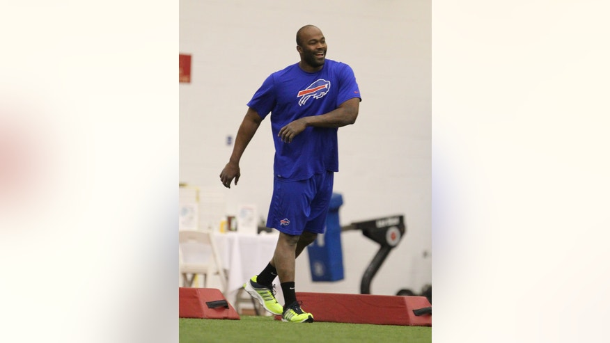 Buffalo Bills' Mario Williams stretches at the start of the team's voluntary offseason conditioning program at the team's NFL football training facility in Orchard Park, N.Y., Tuesday, April 2, 2013. (AP Photo/Bill Wippert)
