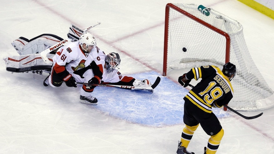Boston Bruins center Tyler Seguin puts the puck in the net past Ottawa Senators goalie Robin Lehner (40) and left wing Andre Benoit (61) in the first period of an NHL hockey game in Boston, Tuesday, April 2, 2013. (AP Photo/Elise Amendola)